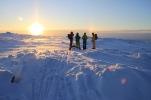Färgglada och glada skidåkare poserar vackert framför solnedgången.